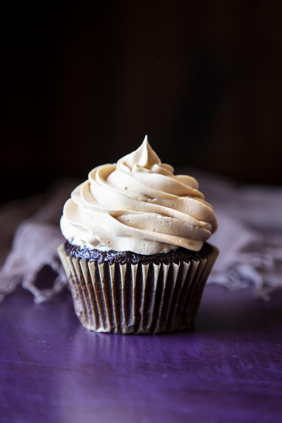 A chocolate cupcake with peanut butter frosting on top