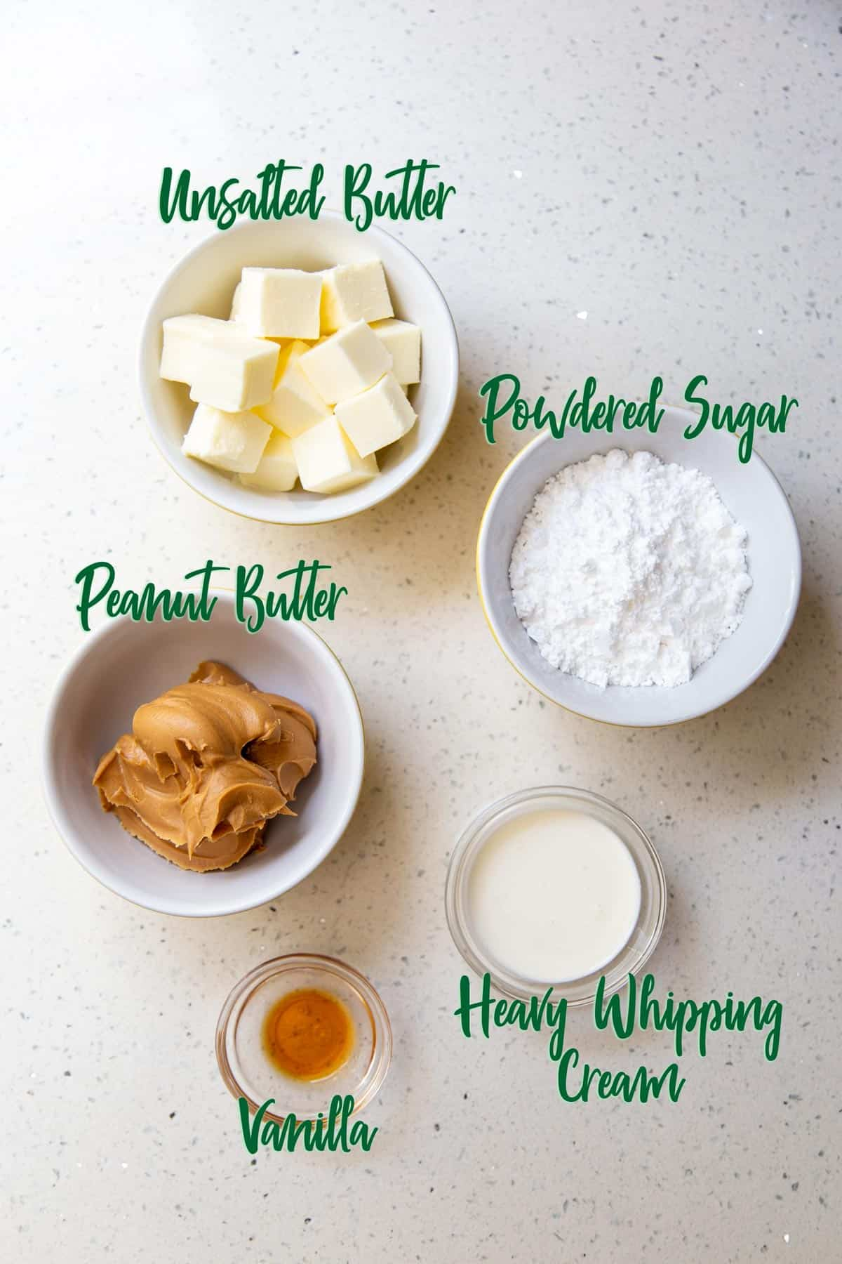 Ingredients for frosting in bowls on a white countertop