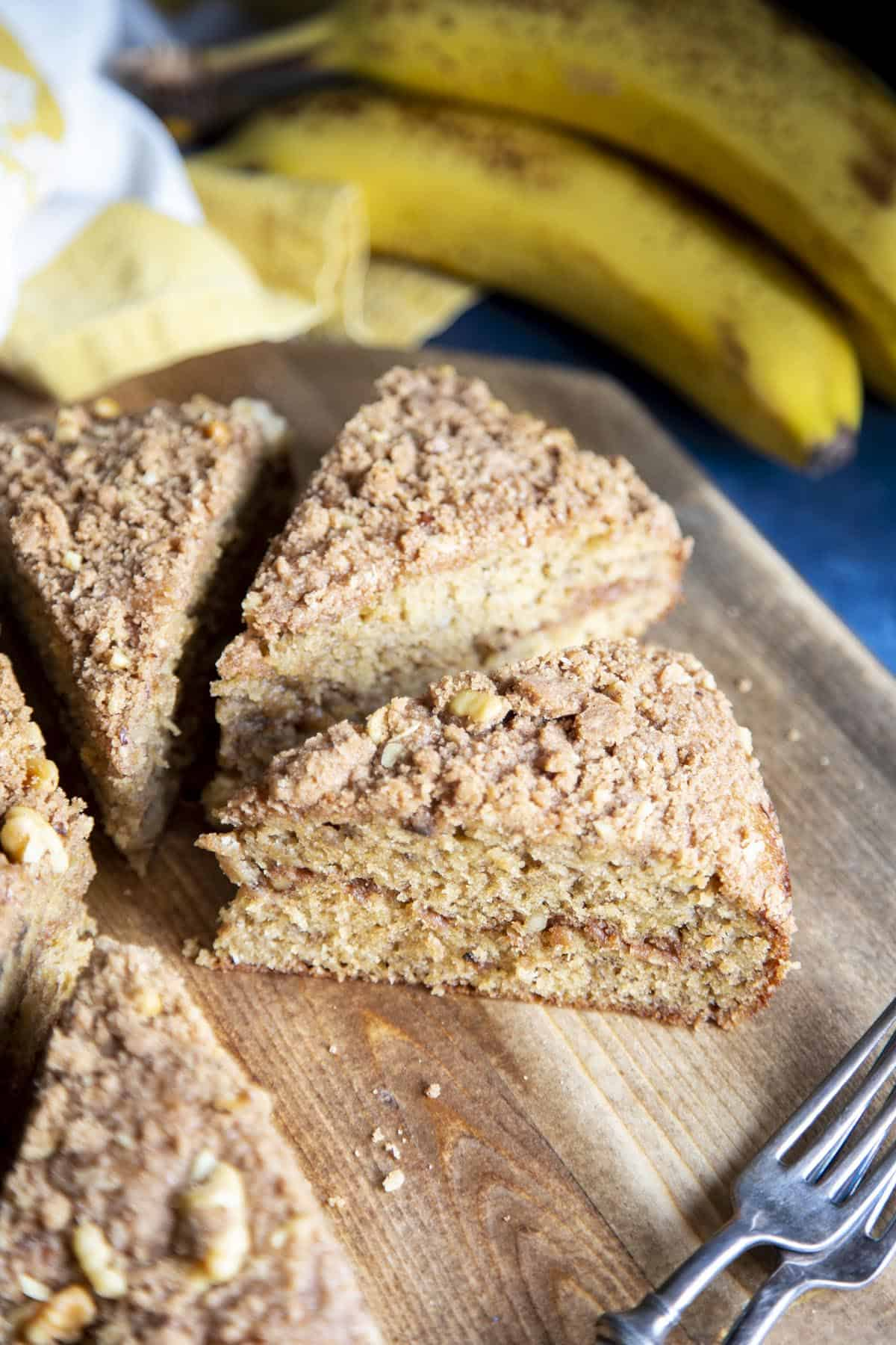 Slices of banana coffee cake on a wooden board.