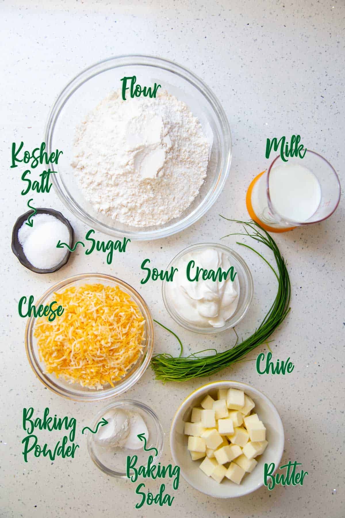 Ingredients for cheese biscuits on a white countertop.