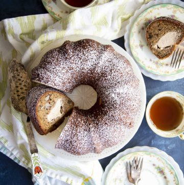 A sliced banana bundt cake on a cake stand, with tea and cake slice on plates surrounding it.