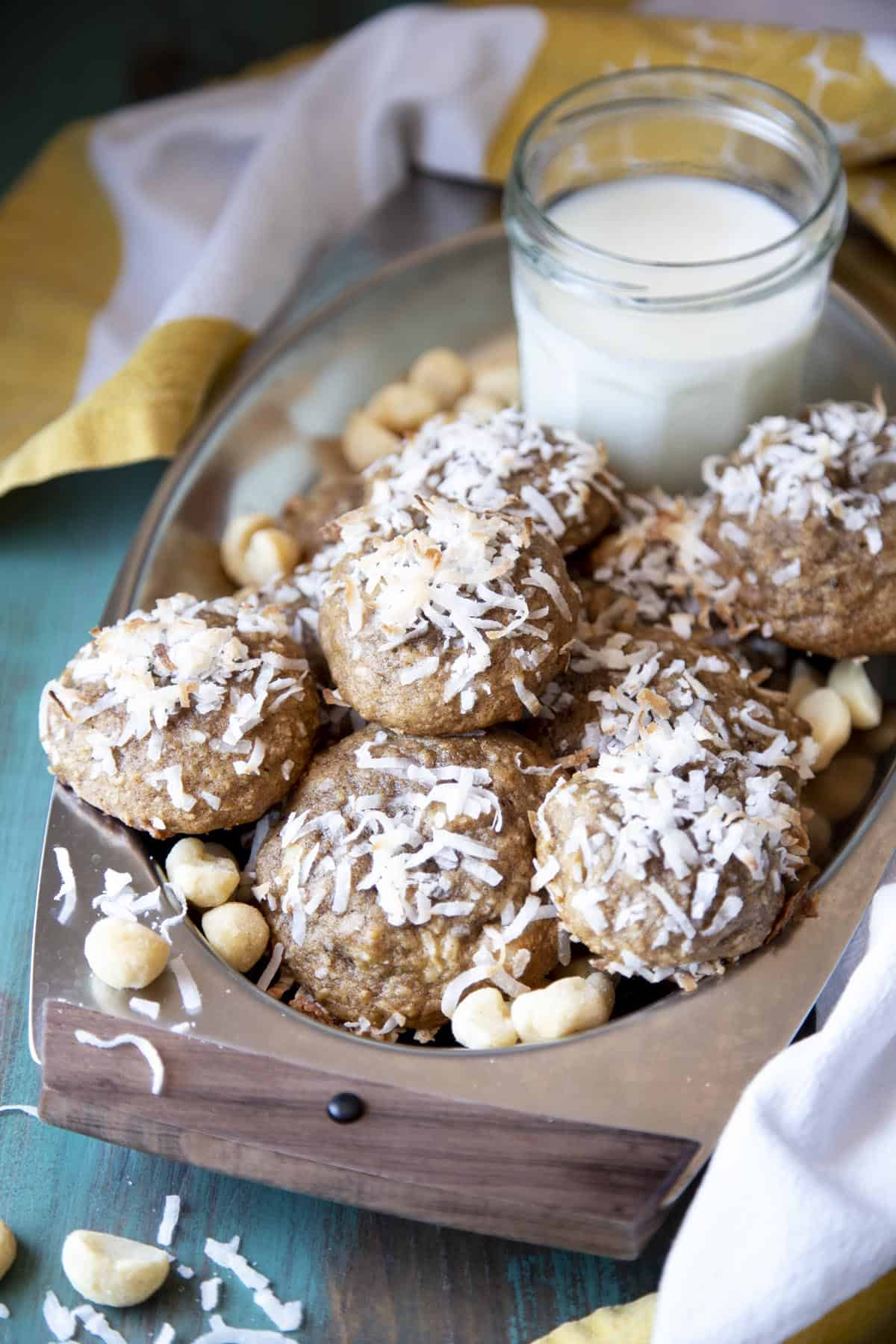 Banana cookies in a serving tray with a glass of milk.