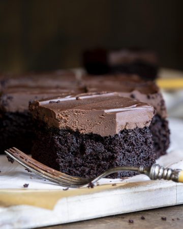 A slice a chocolate cake with chocolate ganache with a fork in front.