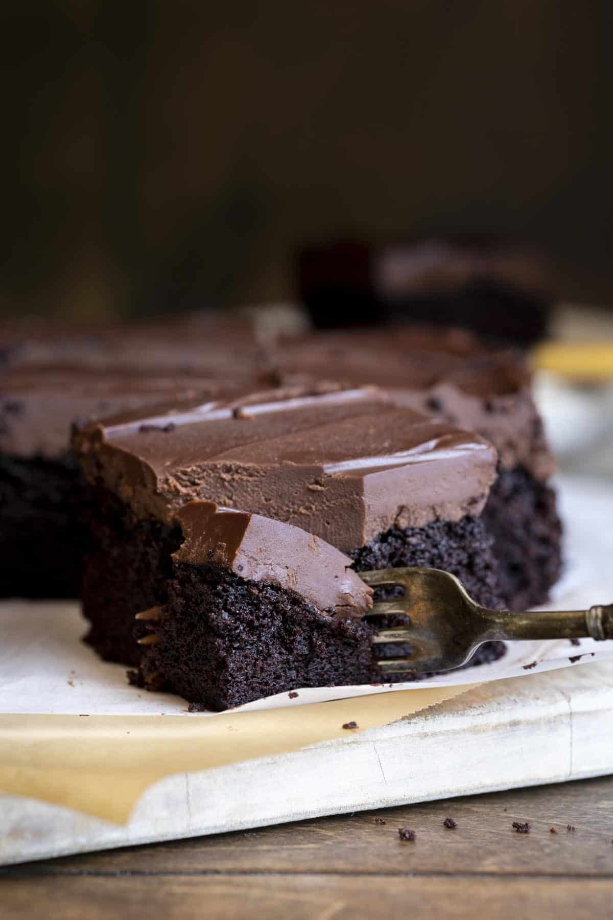 A fork is cutting into a slice of chocolate olive oil cake.