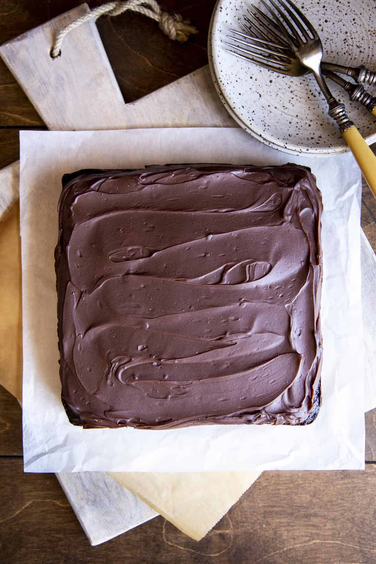 Olive Oil Chocolate Cake with chocolate ganache spread on top sitting on a wooden board.