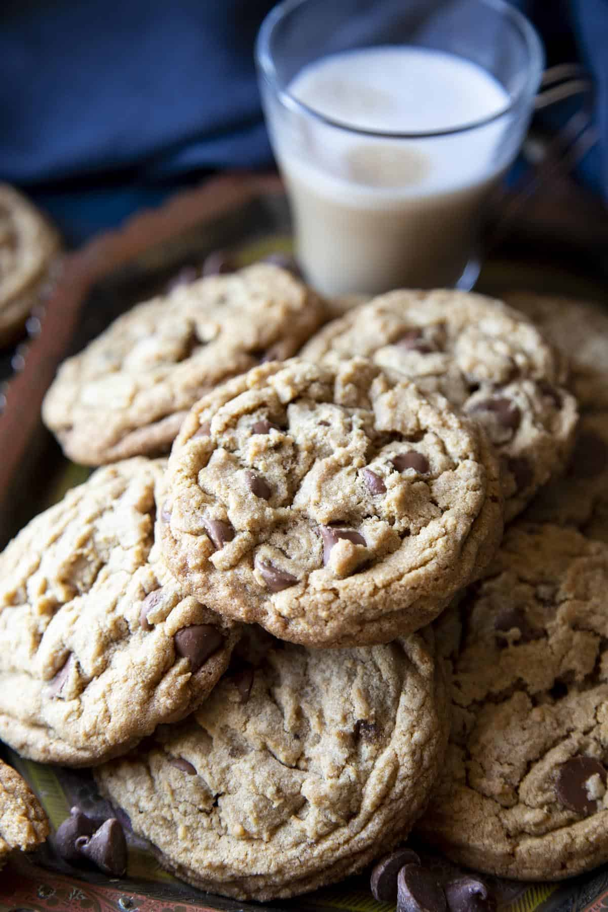A tray of brown butter chocolate chip cookies with a glass of coffee.
