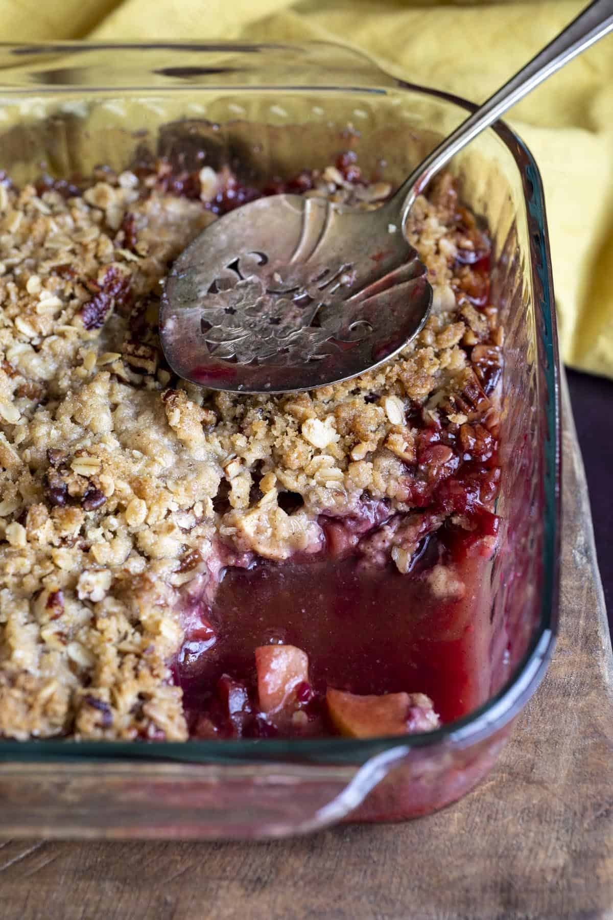 Apple and plum crumble in a glass baking pan, a scoop has been served.