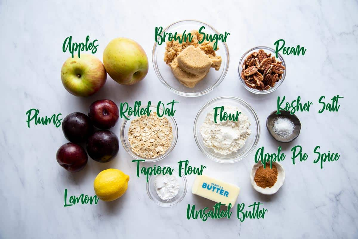 Ingredients for apple and plum crumble on a marble surface.